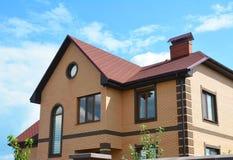 Casa con mattoni a vista con il sistema della grondaia della pioggia della finestra della soffitta e l'asfalto rosso Immagini Stock