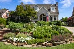 Casa con mattoni a vista multipla grigia del timpano con il giardino di rocce variopinto in bandiera americana anteriore di volo fotografia stock libera da diritti