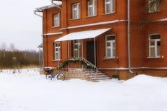 Casa con mattoni a vista nell'inverno, bici parcheggiata fotografia stock