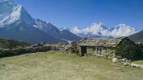 Casa con mattoni a vista semplice nella catena montuosa dell'Himalaya fotografie stock libere da diritti