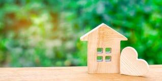 Casa con un corazón de madera Casa de amantes Vivienda asequible para las familias jovenes Casa del día del ` s de la tarjeta del fotografía de archivo