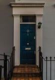 Casa con una puerta verde con un golpeador plateado Imagen de archivo
