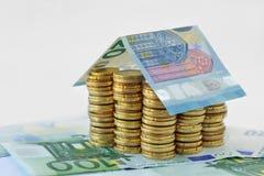 Casa construida con las monedas y los billetes de banco euro imagenes de archivo