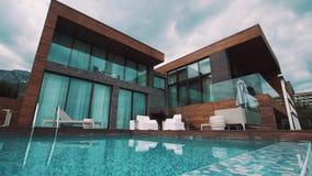 Casa costosa della località di soggiorno con il raccordo di legno e davanti allo stagno ed alle montagne video d archivio
