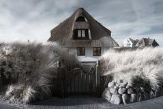 Casa cubierta con paja. Infrarrojo. Imagen de archivo libre de regalías
