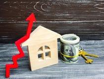 Casa, dólares e chaves de madeira com uma seta vermelha acima Conceito de h imagens de stock