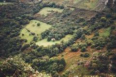 Casa da névoa da manhã nos picos de montanha na paisagem natural O vale verde no céu dramático nevoento do fundo, montanha cobre  Foto de Stock