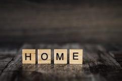 A casa da palavra feita de cubos de madeira brilhantes com letras pretas na Imagens de Stock Royalty Free