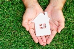 Casa da posse da mão contra o campo verde Fotografia de Stock Royalty Free