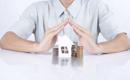 Casa da proteção da mão do vendedor do negócio com casa do conceito do dinheiro Imagem de Stock