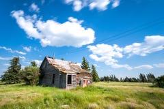 Casa da quinta abandonada velha da pradaria cercada por árvores, pela grama alta e pelo céu azul fotos de stock