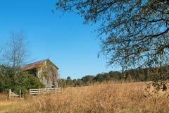 A casa da quinta da degradação coberto de vegetação com as videiras senta-se em Georgia Field imagem de stock