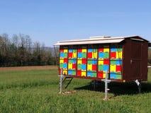 Casa de abeja colorida en un campo Foto de archivo