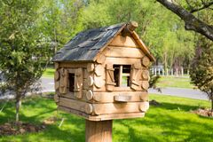 Casa de barras de madeira com Windows como um alimentador do pássaro foto de stock royalty free