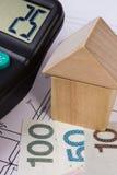Casa de blocos de madeira e do dinheiro polonês com a calculadora no desenho de construção, conceito da casa da construção Fotografia de Stock Royalty Free