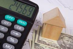 Casa de blocos e do dólar de madeira com a calculadora no desenho de construção, conceito das moedas da casa da construção Foto de Stock Royalty Free