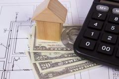 Casa de blocos e do dólar de madeira com a calculadora no desenho de construção, conceito das moedas da casa da construção Fotos de Stock Royalty Free