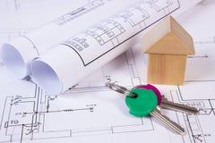 Casa de bloques de madera, rollos de diagramas y llaves en el dibujo de construcción de la casa Foto de archivo