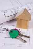 Casa de bloques de madera, rollos de diagramas y llaves en el dibujo de construcción de la casa Fotografía de archivo libre de regalías