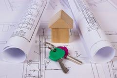 Casa de bloques de madera, rollos de diagramas y llaves en el dibujo de construcción de la casa Fotos de archivo