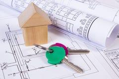 Casa de bloques de madera, rollos de diagramas y llaves en el dibujo de construcción de la casa Imagen de archivo libre de regalías