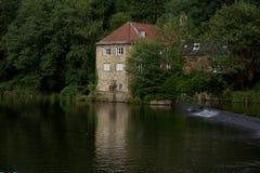 Casa de bomba ao lado completamente de um banco de rio imagens de stock royalty free