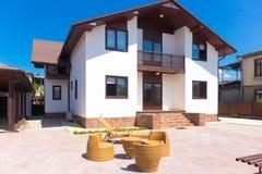 Casa de campo agradável com mobília de vime no jardim da frente Foto de Stock