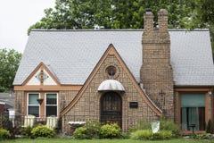 Casa de campo amarela bonita do tijolo com chaminé e toldo dobro e janela redonda sobre a porta - bandeira do trabalho e banho de imagem de stock royalty free