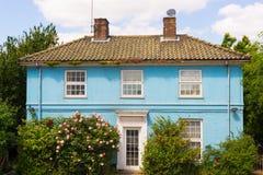 Casa de campo azul com as janelas brancas cercadas pelo jardim Imagem de Stock