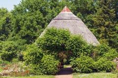 Casa de campo cobrida com sapê em um parque Imagem de Stock