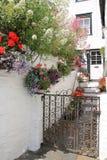 Casa de campo com plantas em pasta e as cestas de suspensão em Polperro no verão foto de stock
