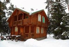 Casa de campo de madeira na madeira do inverno fotografia de stock