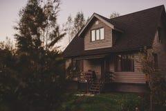 Casa de campo de madera marrón rústica por la tarde del otoño Foto de archivo libre de regalías