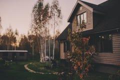 Casa de campo de madera marrón rústica por la tarde del otoño Fotos de archivo libres de regalías