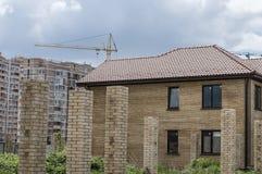 Casa de campo destacada em um fundo de uma construção de vários andares fotografia de stock