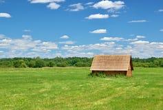 Casa de campo de madeira no prado Imagens de Stock Royalty Free