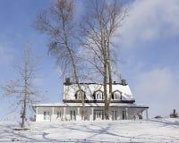 Casa de campo de madera blanca con el tejado negro nevoso en paisaje del invierno fotos de archivo libres de regalías