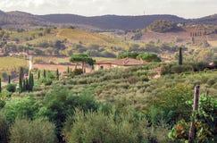 Casa de campo na paisagem rural de Toscânia com árvores do jardim, montes verdes Campo italiano fotos de stock royalty free