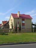 Casa de campo nova atrás da parede de tijolo Foto de Stock Royalty Free