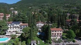 Casa de campo Panorama do lago lindo Garda cercado por montanhas, Itália Tiro video com zangão video estoque