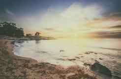 Casa de campo vermelha na frente marítima no nascer do sol com sentimento do vintage Fotos de Stock