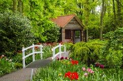 Casa de campo y puente blanco en los jardines de Keukenhof foto de archivo libre de regalías