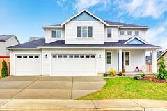 Casa de dois níveis luxuosa exterior com garagem e a entrada de automóveis concreta imagens de stock royalty free