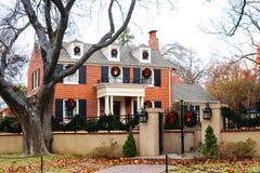 Casa de dos pisos del ladrillo rojo en vecindad residencial frondosa exclusiva con la cerca y la puerta del hierro adornadas mara imagenes de archivo
