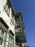 Casa de dos pisos muy vieja con el balcón foto de archivo