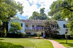 Casa de duas histórias com bandeira americana e bandeiras para 4o julho com ajardinar bonito e árvores bonitas contra o céu azul  Foto de Stock Royalty Free