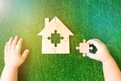 Casa de enigmas de madeira, as mãos da criança, o elemento faltante na perspectiva da grama verde artificial fotos de stock