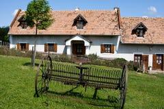 Casa de la aldea con el rastrillo Foto de archivo libre de regalías