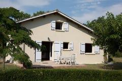 Casa de la familia con las ventanas azules en el jardín Imagen de archivo