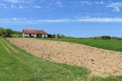 Casa de la granja y pista cultivada Imagen de archivo libre de regalías
